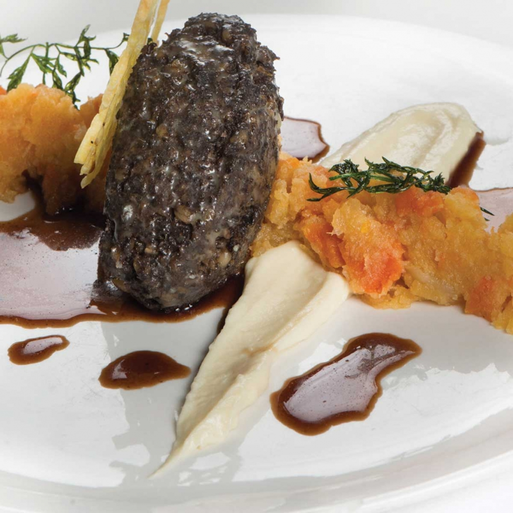 Haggis is a savoury pudding containing sheep's pluck, minced with onion, oatmeal, suet, spices, and salt, mixed with stock, and cooked while traditionally encased in the animal's stomach though now often in an artificial casing instead.